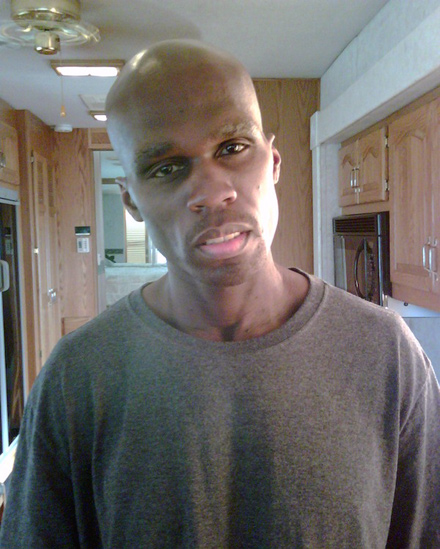 A very slim 50 Cent posing in a kitchen, 54 pounds lighter