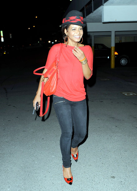 Christina Milian laughing in her little black and red top hat