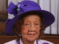 Dorothy Height styling in a purple dress and royal purple hat