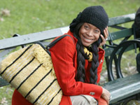 Erykah Badu sitting on a park bench, red coat, black hat, and pigtail wig