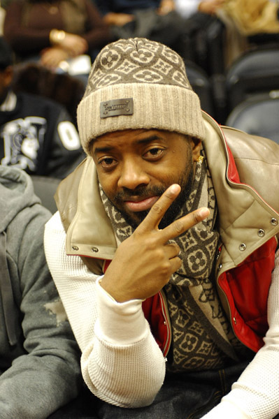Jermaine Dupri throws the peace sign at a Hawks/Nuggets game
