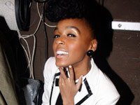 Janelle Monae sitting in her dressing room taking a Poland Spring break.
