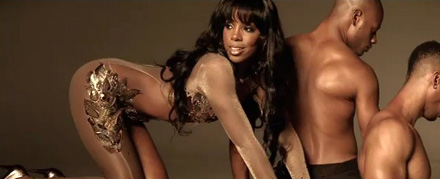 Kelly Rowland in arches her butt on a table