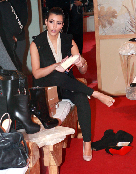 Kim Kardashian admires the patent leather on a pair of shoes in a Beverly Hills shop
