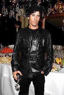 Steven Klein in a leather jacket, with glass of wine in hand