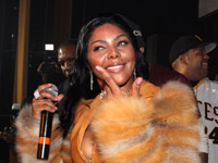 Lil Kim in tan fur and leather jacket on stage at M2 Mansion