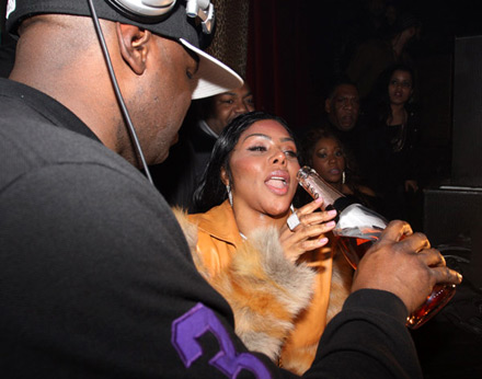 Lil Kim grabs a bottle of Rose champagne