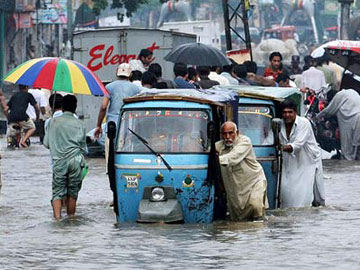 Pakistan - Cyclone Yemyin - Man pushing car through flooded street