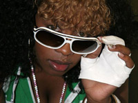 Remy Ma peeks from behind white sunglasses