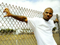 The Game leaning on a fence